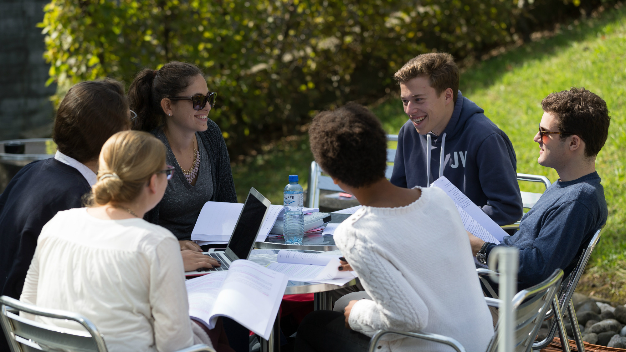 Students sitting in the sun between the Main Building and the Library Building at the University of St.Gallen (HSG)
